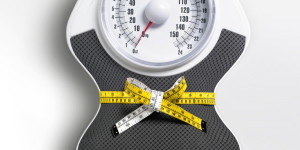 Tape measure squeezing scales to form waist